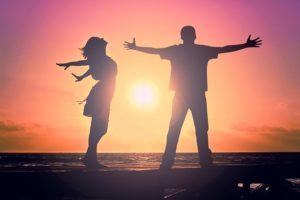 Dos jóvenes bailando sobre la arena en una puesta de sol